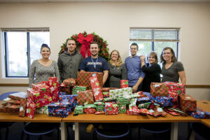Give To Win: Explorer Newspaper staff, from left, Jaime Hood, Chris Flora, J.D. Fitzgerald, Thelma Grimes, Brandon Hays, Grace Heike and Kate Long gather in front of the presents at ICS, which were donated for the paper's Give to Win promotion. - Randy Metcalf/The Explorer