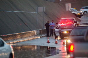 Northwest Storms: A Marana police office blocks off a flooded area at the Orange Grove Road and I-10 underpass due to flooding. - J.D. Fitzgerald/The Explorer