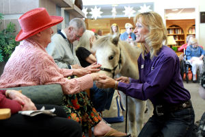 Little Hooves And Big Hearts Visits Clare Bridge: Tammy Mockbee, a co-founder of Little Hooves and Big Hearts, helps Clare Bridge resident Myra Pavlik get close and pet Lilly, a miniature horse.  - Randy Metcalf/The Explorer