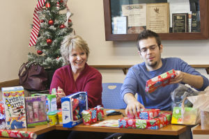 Give To Win: The Explorer Newspaper's Bobbi Paley and Brandon Hays organize and wrap presents at Interfaith Community Services office. - Randy Metcalf/The Explorer