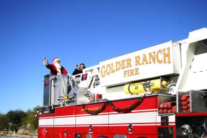 Oro Valley Holiday Parade 2014: To end the lengthy parade, viewers were excited to see Santa Claus on top of the Golder Ranch Fire engine. - Thelma Grimes/The Explorer