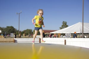 Marana Pumpkin Patch: Haylee Arnold, 4, jumps on the inflated mat at the Marana Pumpkin Patch. - Hannah McLeod/The Explorer
