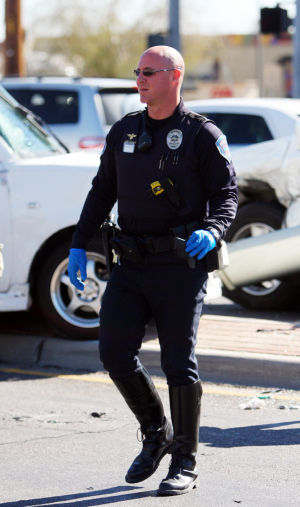 Marana Police Department: A Marana Police Officers retrieves a weapon found at the scene of a car accident.