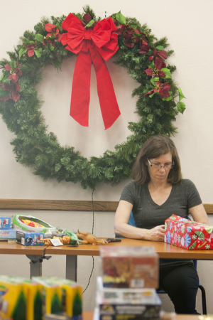 Give To Win: Explorer Newspaper staff member Kate Long wraps a gift in one of the conference rooms at Interfaith Community Services' main office. - Randy Metcalf/The Explorer
