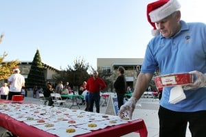 Marana Holiday Tree Lighting: Benny Benson with the Marana Optimist Club places out free cookies. The club gave out free hot chocolate and about 600 cookies throughout the night, Saturday.  - Randy Metcalf/The Explorer