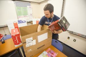 Give To Win: Explorer Newspaper staff member J.D. Fitzgerald unpacks presents to be wrapped, which will be given to families in need this season. - Randy Metcalf/The Explorer