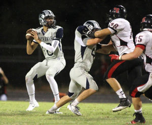Ironwood Ridge Vs Liberty High Football: Ironwood Ridge High School's quarterback Austin Campbell looks for an open receiver as Cole McLafferty blocks a Libery Lion. - Randy Metcalf/The Explorer