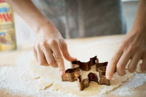 Holiday Baking: Woman making organic Christmas cookies, cutting dough with a cookie cutter.