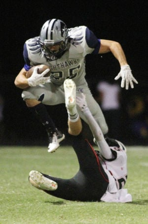 Ironwood Ridge Vs Liberty High Football: Ironwood Ridge High School's Christopher Babyak gets some air as he tries to clear a Liberty player during Friday night's game. - Randy Metcalf/The Explorer