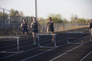 MHS Track: Sydney Madrid begins her leap over hurdle in the 300 meter hurdle race. Madrid ended up easily winning the event.  - Hannah McLeod/The Explorer