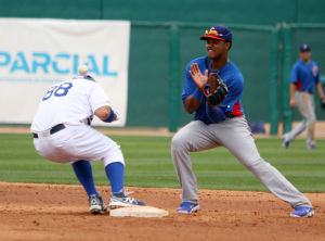Spring Training: Cubs' shortstop Starlin Castro bobbles the ball as a Dodgers player tries to avoid getting hit.  - Randy Metcalf/The Explorer