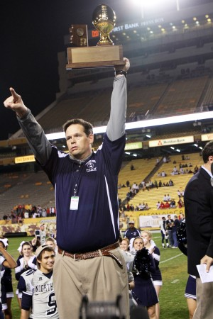 Ironwood Ridge Wins Division II State Football: Coach Matt Johnson hoists the trophy high while pointing to fans after the Division II State Championship victory.  - Jon Grimes/Special to the Explorer