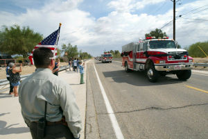 William Warneke: The fire truck carrying the body of William Warneke, one of the 19 firefighters killed in the Yarnell Hill fire, travels from the Marana Airport to the Marana Mortuary Cemetery as people pay their respects along Sanders Road. - Randy Metcalf/The Explorer