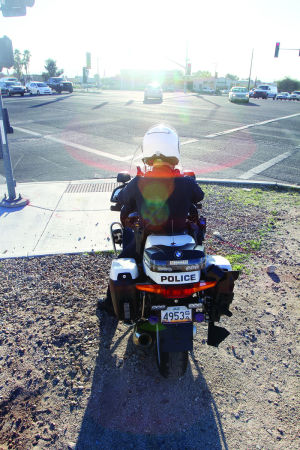 HiVE Deployment: Oro Valley motor officer Brian Kleinberg watches traffic at the intersection of Oracle and Magee roads during the department's High Visibility Enforcement deployment last week. - Randy Metcalf/The Explorer