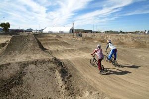 Xtreme Fun Spot At Sports Park: Dylon Vaughn, left, and Corben Sharrah, make their way around the new BMX course at Sports Park.  - Randy Metcalf/The Explorer