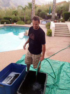 Tucson Grill Cleaning: Lonnie Campbell, an associate of Tucson Grill Cleaning, sprays water into a tub where parts of a barbeque soak. Cleaning a barbeque can take from 1.5 to 3.5 hours.