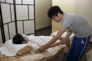 AZ Massage Center: Guang Li (Andy) shows how to massage an arm on co-worker, Yan Sailer, at AZ Massage Center.  - Hannah McLeod/The Explorer