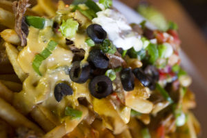 The Lodge Sasquatch Kitchen: The Wildcat comes with skin-on fries covered with shredded beef, the Lodge's cheese sauce, black olives, sour cream, pico de gallo, guacamole, green onions and jalapeños.  - Randy Metcalf/The Explorer