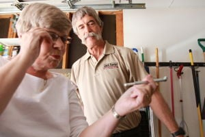 Car Care Clinic: Rick Furrier looks on as Beverly Hall checks the tire pressure gauge.  - Randy Metcalf/The Explorer