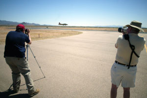 Wings Of Freedom Tour: Tucsonan Jeff Hoffman, left, and SaddleBrooke resident Bill Todd take photos as the B17 lands at the Marana Regional Airport Friday.  - Randy Metcalf/The Explorer