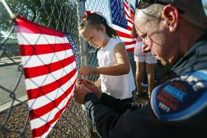 Flag Day 1: Marana police officer Brad Clifford helps kindergartener Alexa Corona pin up an American flag on a fence at Coyote Trail Elementary School last Friday. Hanging the flags is part of the school's annual 9/11 Spirit Day which it has held every year for the past nine years.  - Randy Metcalf/The Explorer