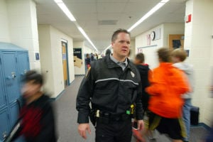 Oro Valley School Resource Officer Program: Oro Valley School Resource Officer Kevin Mattocks stands in the hallway as students at Wilson K-8 travel between classes.  - Randy Metcalf/The Explorer