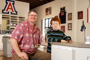 Del Kyger Orthodontics: Dr. Del Kyger and his 8-year-old son, Logan, sit in the Del Kyger Orthodontics office, which is clad with numerous University of Arizona memorabilia, pictures and framed newspaper clippings.  - Randy Metcalf/The Explorer