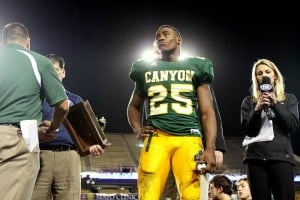 Not This Year : Randy Metcalf/The Explorer,Following Canyon Del Oro's 41-34 loss to Scottsdale Saguaro in the 4A-I state championship football game Saturday, Ka'Deem Carey and a few other seniors from the team await the presentation of the runners-up trophy. CDO had its 27-game winning streak snapped in the contest at Sun Devil Stadium in Tempe.