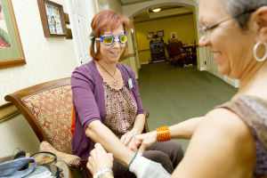 Virtual Dementia Tour: Lisa Burns, who is a certified senior advisor, has goggles, gloves and earphones put on with the help of Shelley Harris, who is the director of sales for Sunrise Senior Living, all with the intent to experience what someone might feel like when they have some form of dementia. - Randy Metcalf/The Explorer