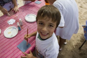 Archaeology History Camp For Kids: Romel Astacio, 6, stops to smiles as he paints onto a tile of white clay at the Archaeology History Camp for Kids at Steam Pump Ranch. - Hannah McLeod/The Explorer