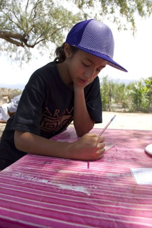 Archaeology History Camp For Kids: Ginelle Astacio, 11, takes her time as she begins to draw an animal onto her tile. - Hannah McLeod/The Explorer