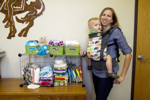 Green Baby Elephant: Tonya Scott displays her online store baby products while holding her one-year-old son, Marshall Scott, in a baby carrier. Scott launched her online website called Green Baby Elephant in 2010. - Hannah McLeod/The Explorer