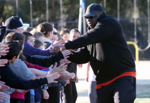Olympic Medalist Michael Bates: Michael Bates runs down the line giving high-fives to students at Mesa Verde Elementary School.  - Randy Metcalf/The Explorer