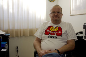 John Matsuks: John Matsuks, 56, shows his appreciation by wearing a Marco's Pizza t-shirt where he was employed before having his second stroke in September. Owner of Marco's Pizza, Jack Ziegler, has ensured Matsuks that his job as a pizza deliveryman will be here for him once he fully recovers. - Hannah McLeod/The Explorer