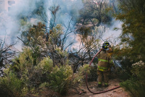 Northwest Fire Extinguishes Brush Fire Near Apartment Complex: Northwest Fire District firefighters extinguish a brush fire near the Dorinda Vista Apartments - J.D. Fitzgerald/The Explorer