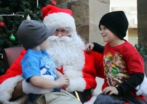 Marana Holiday Tree Lighting: Six-year-old Caleb Mendelsohn, right, and his 3-year-old brother Conner talk to Santa during the Marana festivities Saturday.  - Randy Metcalf/The Explorer