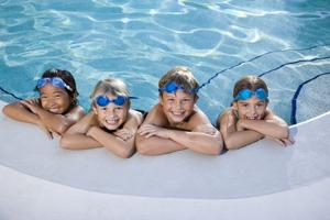 Children Smiling At Edge Of Swimming Pool