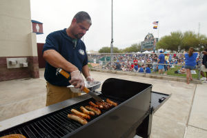 Spring Training: Luis Gutierrez grills up some brats for the concession stand behind center field.  - Randy Metcalf/The Explorer
