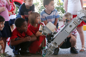 Second Annual First Responders Appreciation Block Party: Children from the St. Mark's Early Childhood Center get a close look at the Pima Regional SWAT Team's robot as it picks up a water bottle. - Randy Metcalf/The Explorer