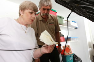 Car Care Clinic: Beverly Hall and Rick Furrier check the oil in her Honda Accord. With the help of Furrier, Hall has formed a womenÕs car care clinic.  - Randy Metcalf/The Explorer
