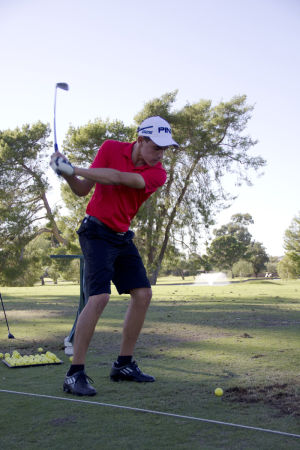CDO Golf: Chris Meyers, a junior, takes a swing at CDO's golf practice. The CDO golf team placed third at the Division II state championship. - Hannah McLeod/The Explorer