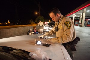 HIOP: Pima County Sheriff Deputy Jamie McNeely sorts out evidence found in a vehicle they pulled over on a traffic stop.  - J.D. Fitzgerald/The Explorer