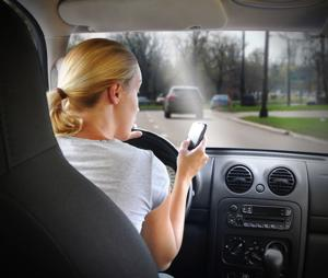 Woman with phone and driving car