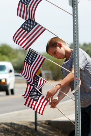 William Warneke Procession: Tyler Crockett, 11, adjusts American flags along the route, which the remains of Granite Mountain Hotshot William Warneke traveled through Marana on the way to his funeral last week. - Randy Metcalf/The Explorer