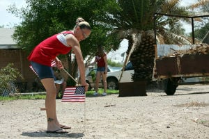 William Warneke Procession: Crystal Bomesberger places an American flag along Moore Road prior to the procession for Granite Mountain Hotshot William Warneke. - Randy Metcalf/The Explorer