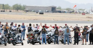 William Warneke Funeral: Motorcyclists hold hands as a group at the Marana Regional Airport before the delivery of the casket of William Warneke. - Hannah McLeod/The Explorer