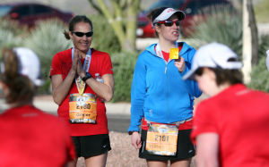 Arizona Distance Classic: Ginger Unwin, left, and Elsbeth Peterson cheer on the runners after they finished second and third place respectively for the women in the 5K race Sunday.  - Randy Metcalf/The Explorer