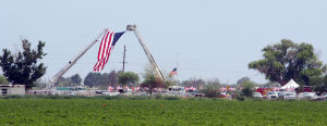 William Warneke Procession: A giant U.S. flag is flown between two fire trucks at the entrance to the Marana Mortuary and Cemetery for the funeral of William Warneke. - Randy Metcalf/The Explorer