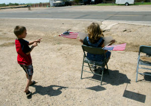 William Warneke Procession: Baiden Riggs, 6, and Tori Bomesberger, 10, prepare their seats and flags for the procession through Marana for Granite Mountain Hotshot William Warneke. - Randy Metcalf/The Explorer