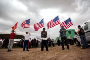 "William Warneke Procession: Members of the ""Legion Riders""hold american flags around the gravesite where Granite Mountain Hotshot William Warneke was buried. - J.D. Fitzgerald/The Explorer"